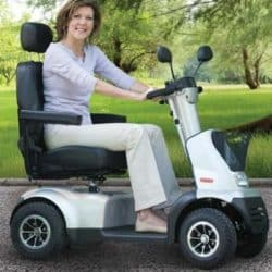 A woman in a light purple shirt and khaki smiles at the camera while sitting in an outdoor scooter.
