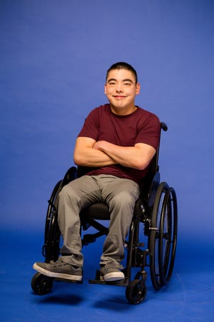 Brennan Srisirikul posing in front of an all blue backdrop while sitting in his wheelchair
