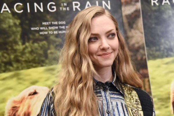 Amanda Seyfriend smiling away from the camera in a black silver and blue button up shirt at a movie premiere