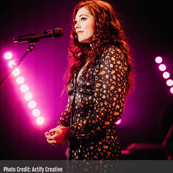Mandy Harvey onstage sideview signing in to microphone bright pink show lights in background