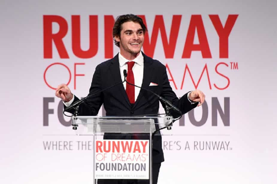 RJ MItte speaks to an audience at a runway event