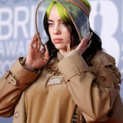 Billie Eilish wearing a burberry visor with long burberry nails and a burberry sweater.