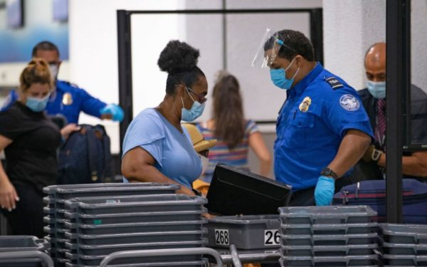 A TSA worker wears a mask while helping travelers get through a security checkpoint at Miami International Airport.
