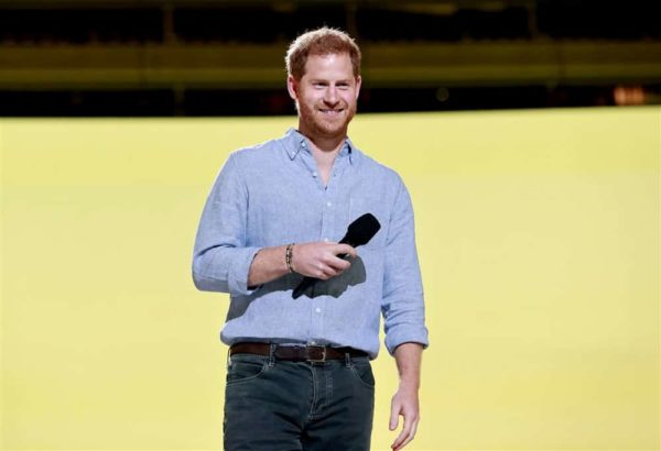 Prince Harry speaking with a microphone in front of a yellow background