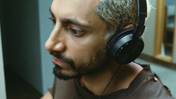 Riz Ahmed wearing head phones and looking away from the camera from the film Sound of metal