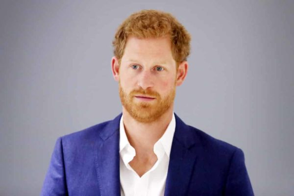 Prince Harry wearing a blue blazer and white shirt while staring away from the camera