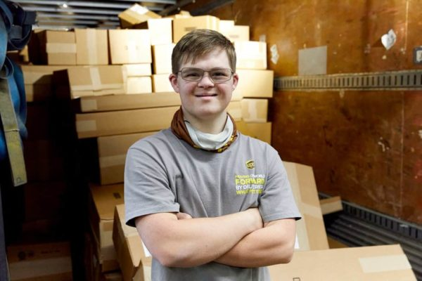 UPS worker with down syndrome lands permanent position and inspires a scholarship. The employee jake is pictured in his uniform in front of a pile of carboard boxes
