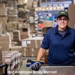 IBVI employee Emily Merced wearing a baseball cap and blue polo work shirt at work in warehouse with cart in front and many boxes stacked behind her