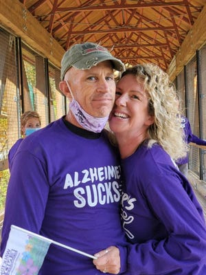 He was diagnosed with Alzheimers in 2018 and retired; a year later, Lisa retired to become his full-time caregiver. Wife and husband photographed in purple while smiling at the camera