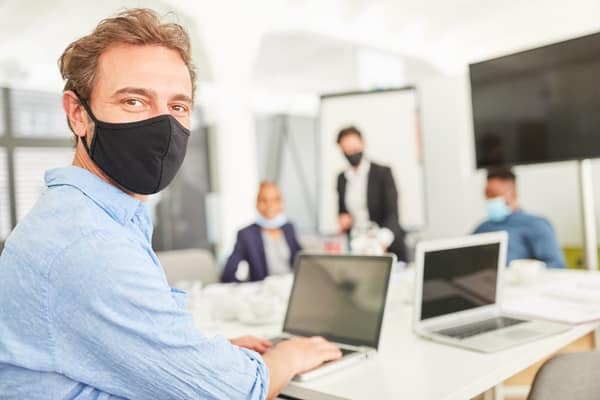 Business man with face mask works on laptop computer