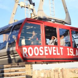 Roosevelt Island tram with group of tourists looking out over river