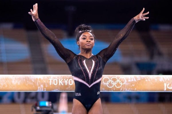 Simone Biles at the olympic games posing with her arms in the air in front of a balance beam