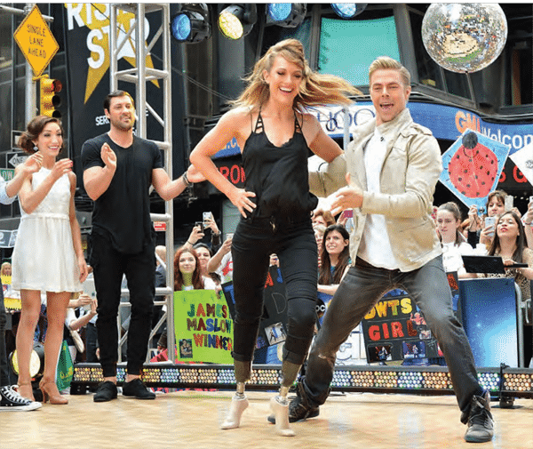 Amy Purdy dancing with Derek Hough in front of live audience outside